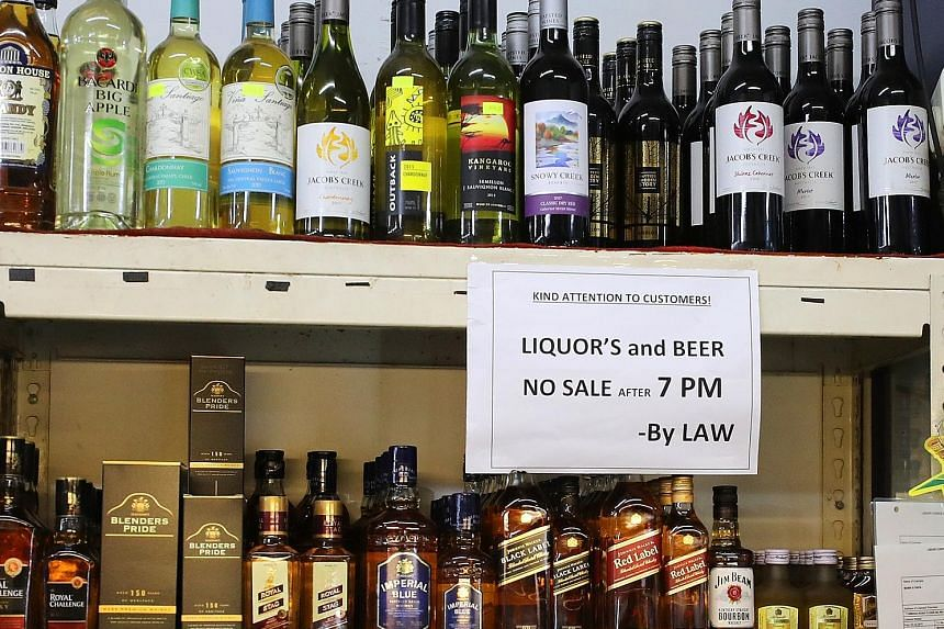 Signs at some liquor stores telling customers of alcohol rules after restricted hours (above). A store assistant selling a can of beer to a customer at about 9pm on a Sunday.