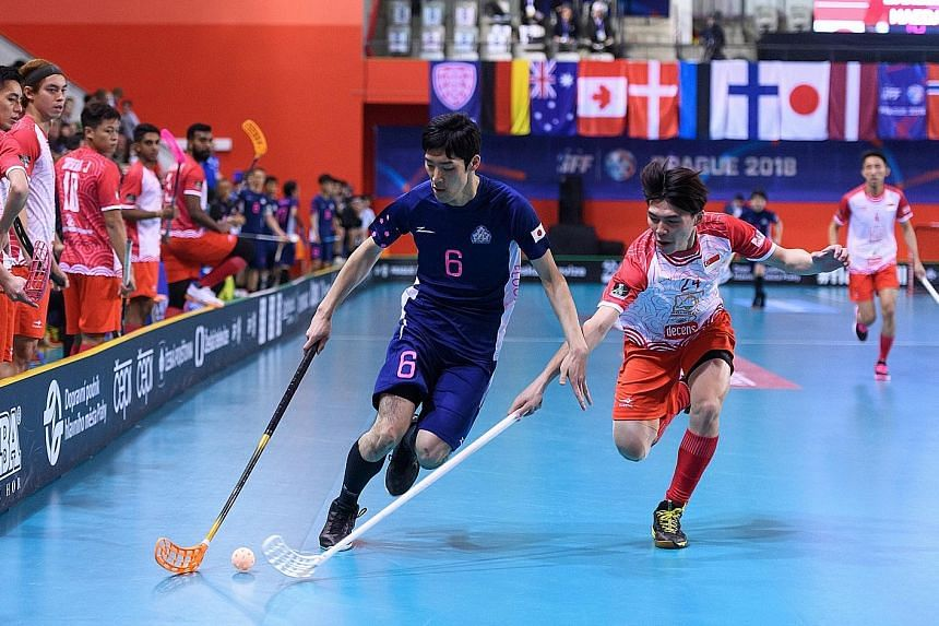 Nicholas Chua (right) and Rikiya Matsumoto tussling for the ball in Singapore's 4-2 loss to Japan yesterday in the play-off for 15th at the World Floorball Championship.