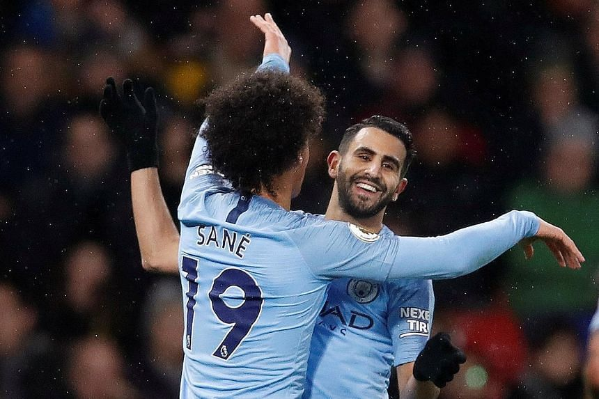 Leroy Sane celebrating with Riyad Mahrez after scoring City's first goal in the 2-1 away win over Watford on Tuesday. The team took their foot off the pedal when leading 2-0 and boss Pep Guardiola will not want a recurrence.