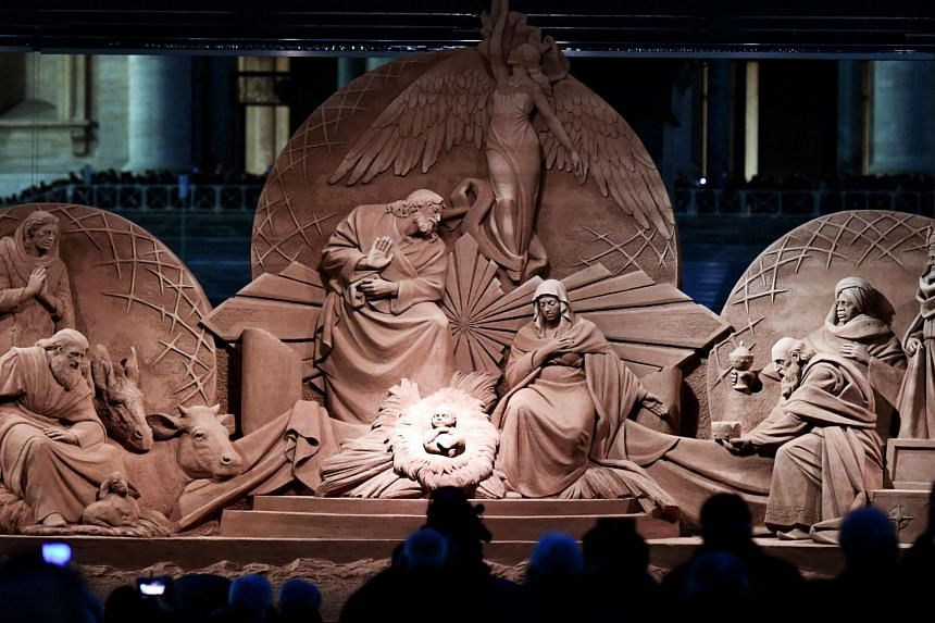 People looking at the sand nativity scene after it was unveiled in St Peter's square at the Vatican, on Dec 7, 2018.
