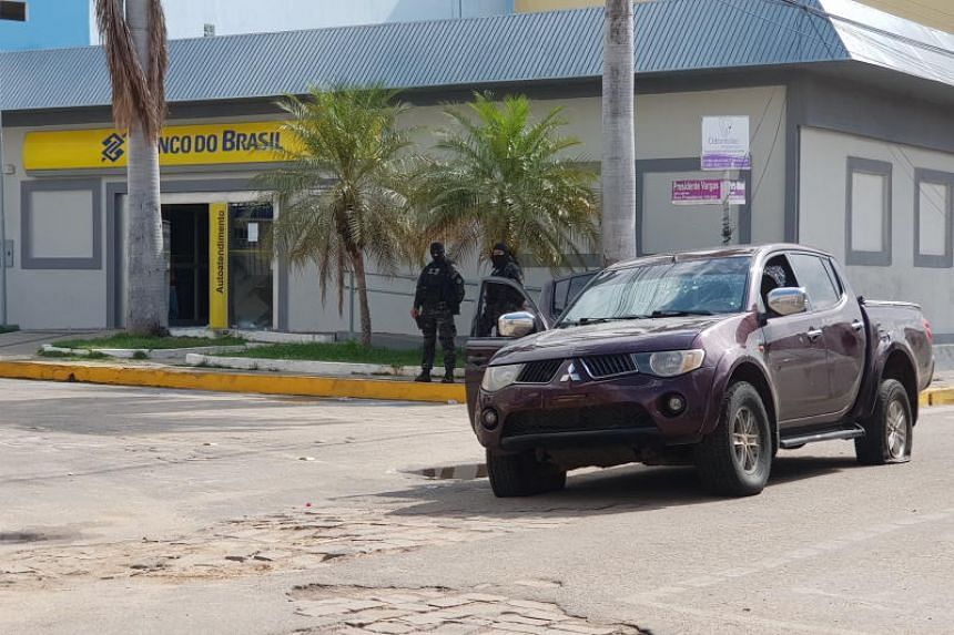 Police officers guarding the exterior of a bank after a shooting, in Milagres, Brazil.