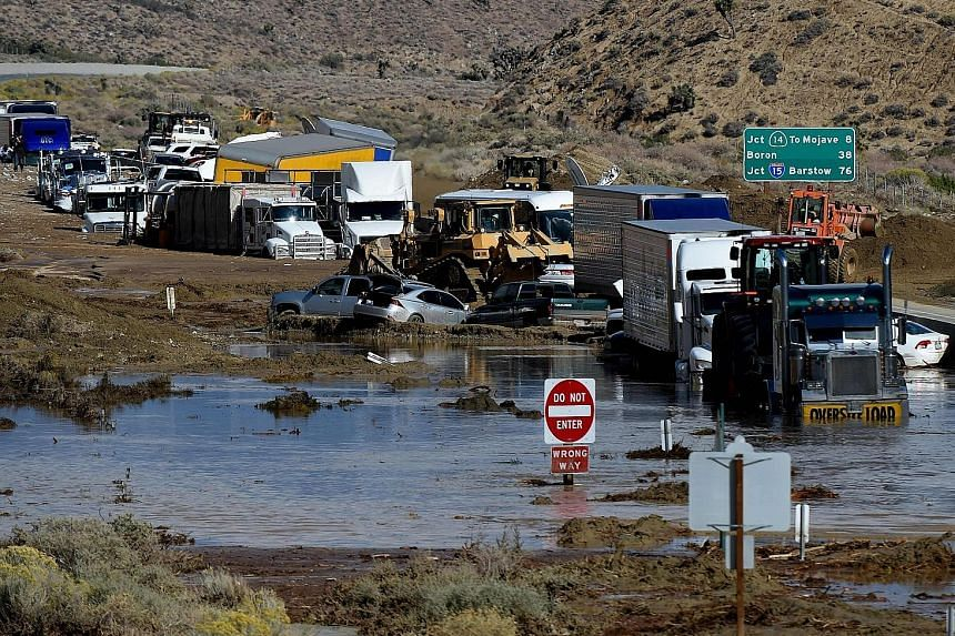 Vehicles stuck on a road, trapped by a mudslide in California. Climate changes pose challenges to investors, the writer says.