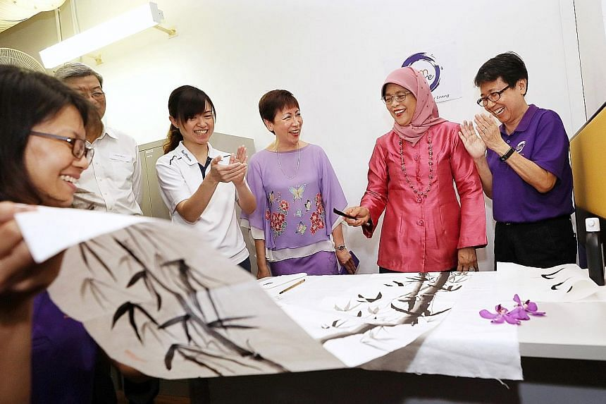 President Halimah Yacob adding two leaves to a Chinese painting at the official opening of Brahm Centre @ MacPherson yesterday. With her are (from right) the centre's counselling and care manager Lily Tan, Brahm Centre founder Angie Chew and MacPhers