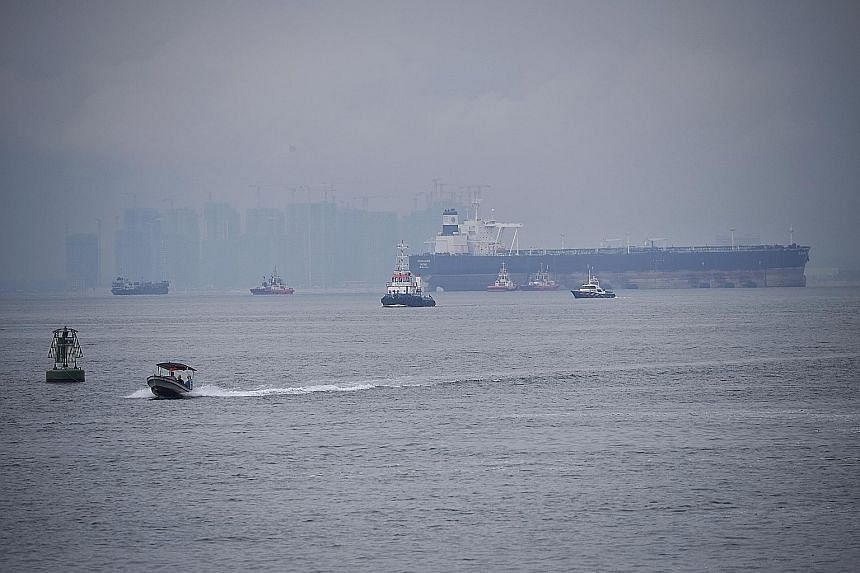 A Singapore Police Coast Guard vessel (far right) patrolling Singapore's territorial waters last Thursday.