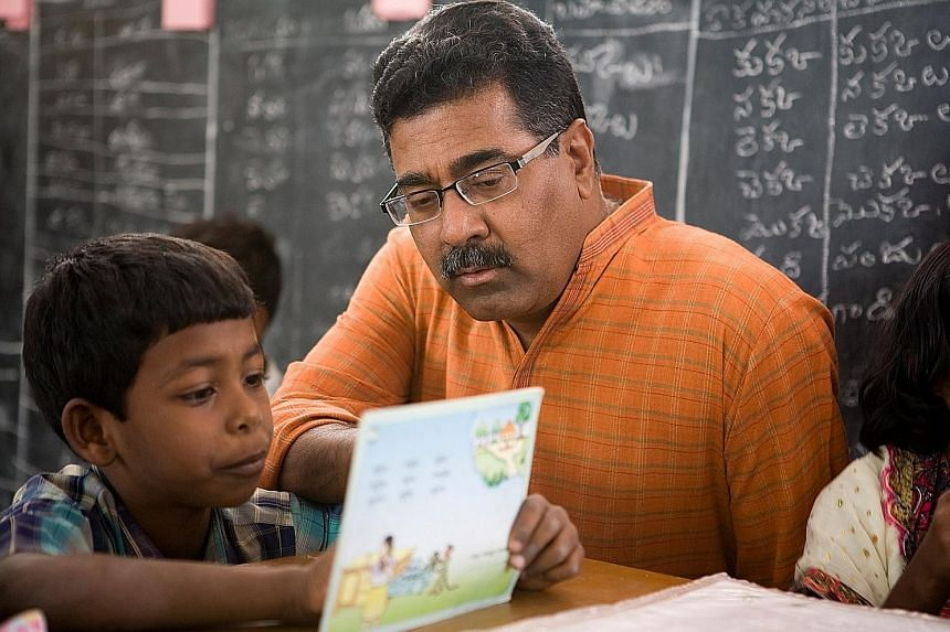 Mr Padmanabha Rao helping a pupil at a school in Andhra Pradesh, India. Mr Rao and his wife, Ms Rama Anumula, together created the educational approach that encourages children to learn on their own. One decade after it was adopted, achievement in re