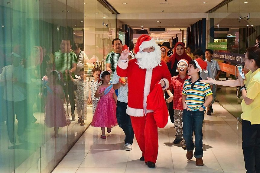 Concorde Hotel Singapore's catering sales director Kenneth Looi, 58, dressing up as Santa Claus to entertain the beneficiaries of The Straits Times School Pocket Money Fund (STSPMF). The hotel organised a Christmas light-up and party to mark its 10th