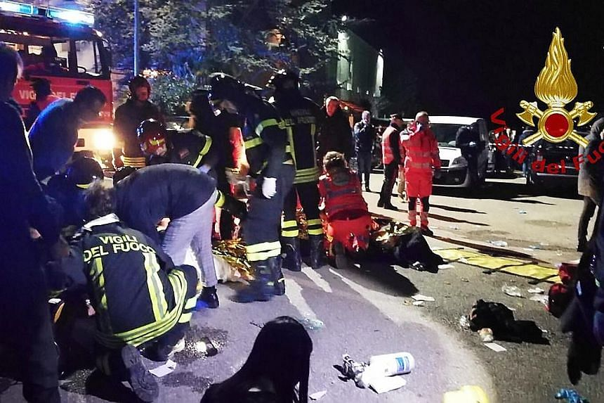 Emergency personnel treating victims after a stampede at a nightclub in the town of Corinaldo, central Italy, in the early hours of yesterday. Media reports said the suspected use of a pepper spray-like substance sparked the chaos at the venue. About