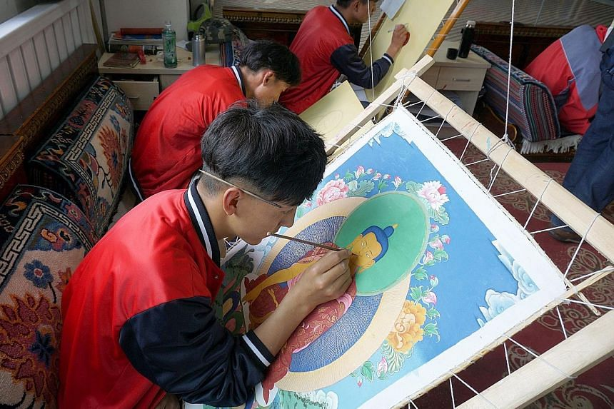 Second-year student Ciwang Nazha, 18, of Lhasa No.2 Secondary Vocational and Technical School engaging in Thangka (Tibetan Buddhist) painting alongside other students.