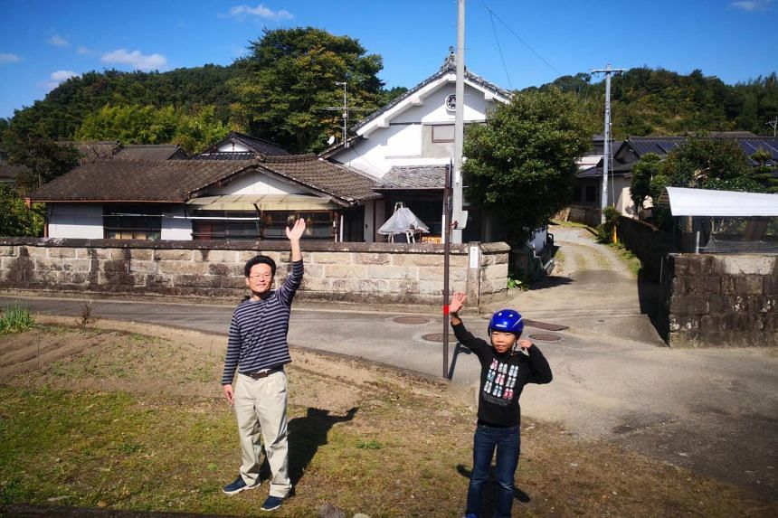 """People along the tracks waving as the train passes by, in a gesture known as """"tewofu-rail""""."""