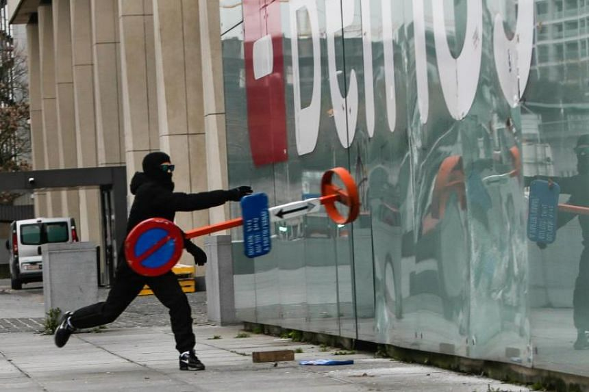 A protestor throws a road sign against the window of the Belfius bank during a copycat 'yellow vest' demonstration on Dec 8, 2018 in Brussels.