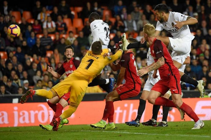 Valencia's French defender Mouctar Diakhaby (top left) scores during the Spanish league football match between Valencia Cf and Sevila FC at Mestalla stadium in Valencia on Dec 8, 2018.