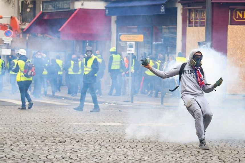 Protestors clash with police forces on Dec 8, 2018 in Paris, during a protest of 'yellow vests' against rising costs of living they blame on high taxes.
