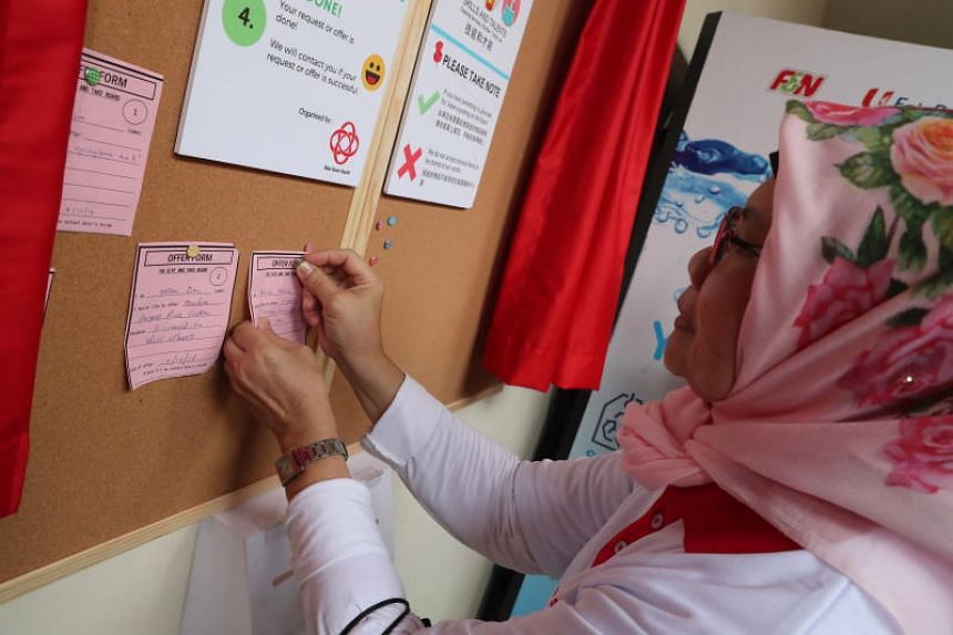 Madam Rohani Hashim, 63, a resident, pinning a form on the board offering a pair roller blades for children.