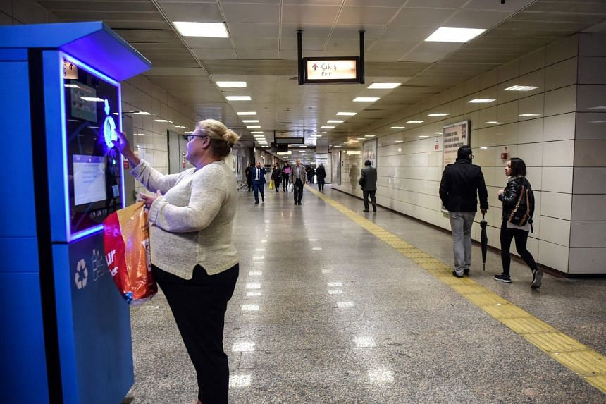 A woman puts a plastic bottle into a vending machine as she waits to take extra credit on her Istanbul card at a metro station on Nov 9, 2018.