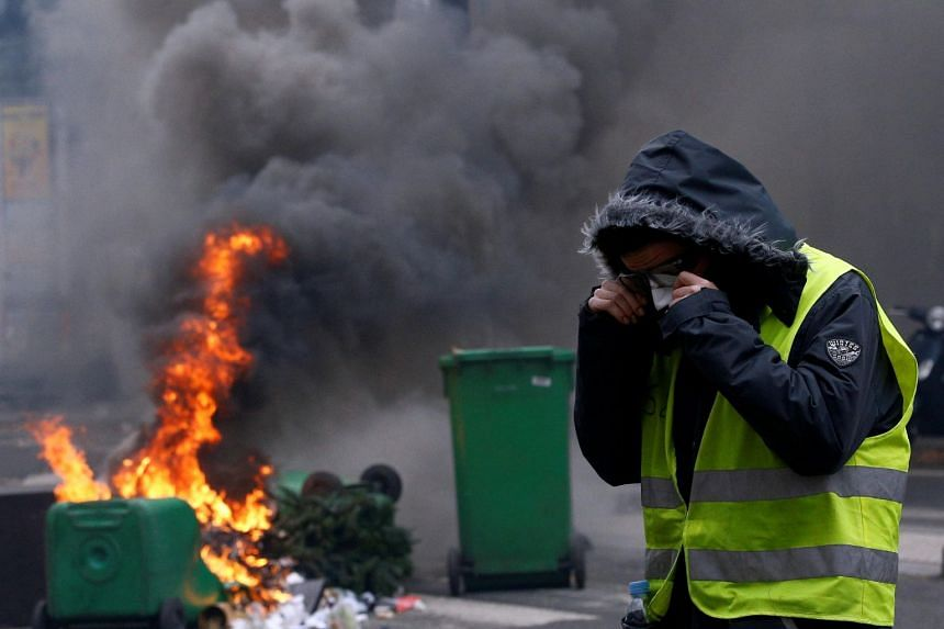 A protester wearing a yellow vest stands next to burning trash bins in a street during clashes with police in Paris, on Dec 8, 2018.
