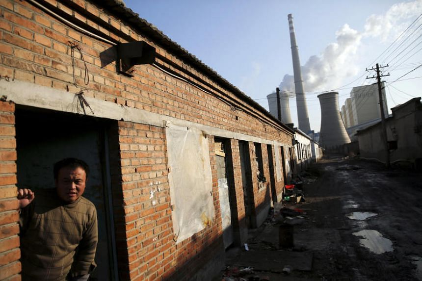 FILE PHOTO: A migrant worker steps out of his accommodation in an area next to a coal-fired power plant in Beijing, China, on Dec 10, 2015.