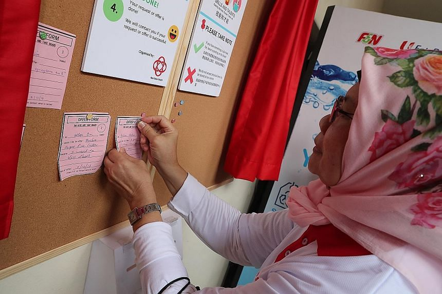 Nee Soon South resident Rohani Hashim pins a note on the new Nee Soon South Community Club Project Give And Take notice board to give away a new pair of inline skates for children. The club launched the notice board yesterday to match residents with