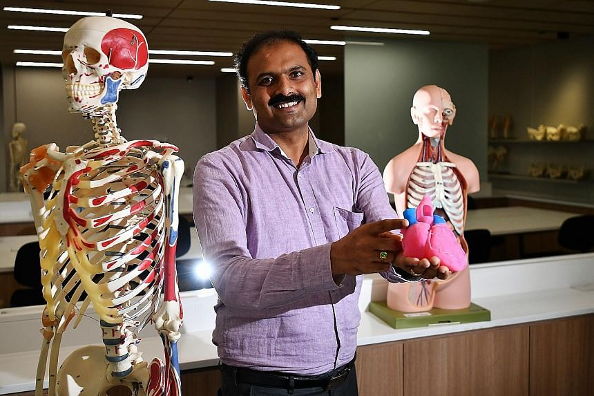 Assistant Professor Reddy Mogali, head of anatomy at NTU's Lee Kong Chian School of Medicine, with a 3D-printed heart. He said such replicas of human organs, made with 3D printers, serve as an additional learning tool for his students, who have until