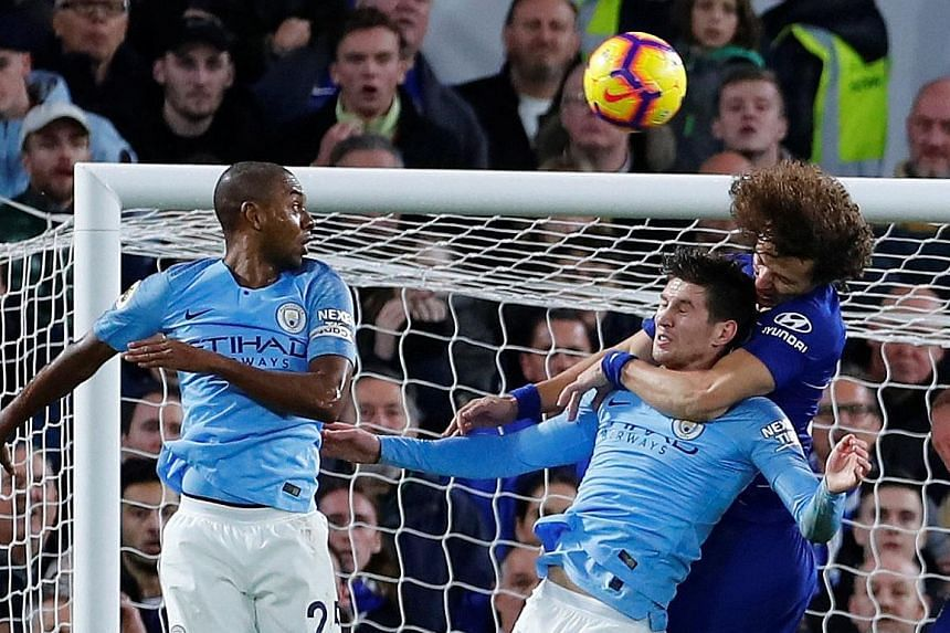 David Luiz, with his left arm wrapped around City defender John Stones, heading in Chelsea's second goal from a corner.