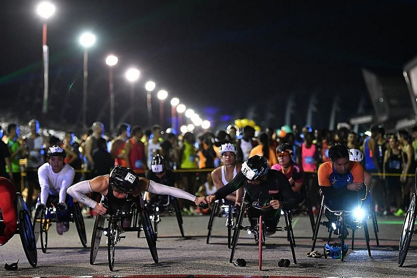 Two elite wheelchair athletes wishing each other well as they line up at the start in front of the main marathon participants.