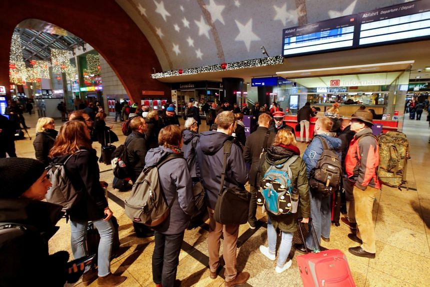 Commuters line up in front of a Deutsche Bahn information counter during a rail workers' strike across the country due to a pay dispute with Deutsche Bahn, in Cologne, Germany, on Dec 10, 2018.