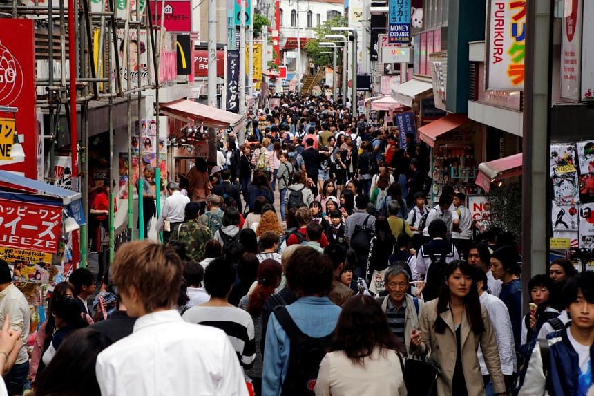 File photo of people walking on a street in a busy shopping district in Tokyo, Japan.