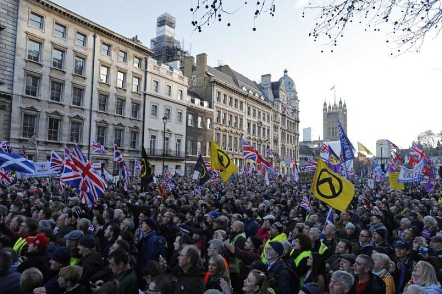 Protesters hold up placards and Union flags as they attend a pro-Brexit rally promoted by the United Kingdom Independence Party in central London on Dec 9, 2018.