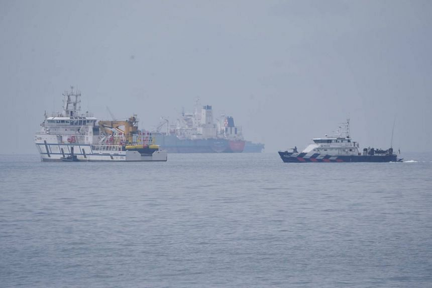 A Singapore Police Coast Guard vessel (right) passes a Malaysian government vessel (left) in the waters between Singapore and Malaysia, on Dec 6, 2018.