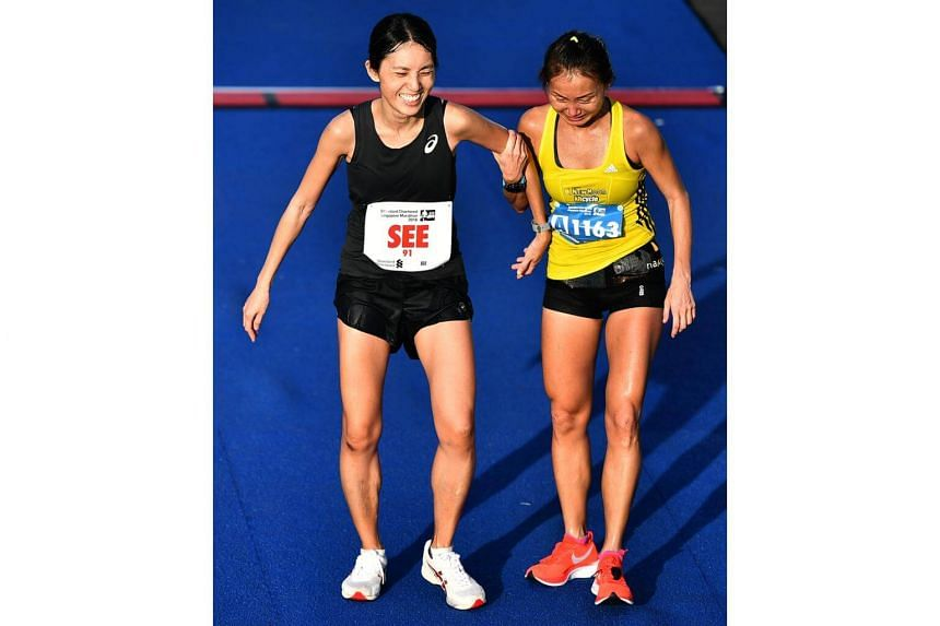 Camaraderie, love and respect at the finish: Lim Baoying, the top local female finisher, helping rival Rachel See when the latter came in second two minutes later.
