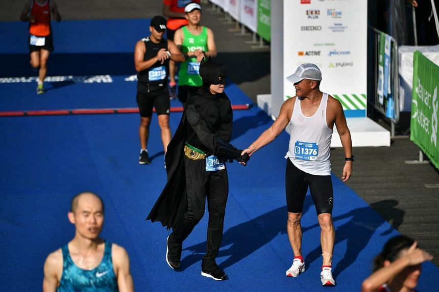 """Camaraderie, love and respect at the finish: """"Batman"""" congratulating a runner dressed in more regular attire."""