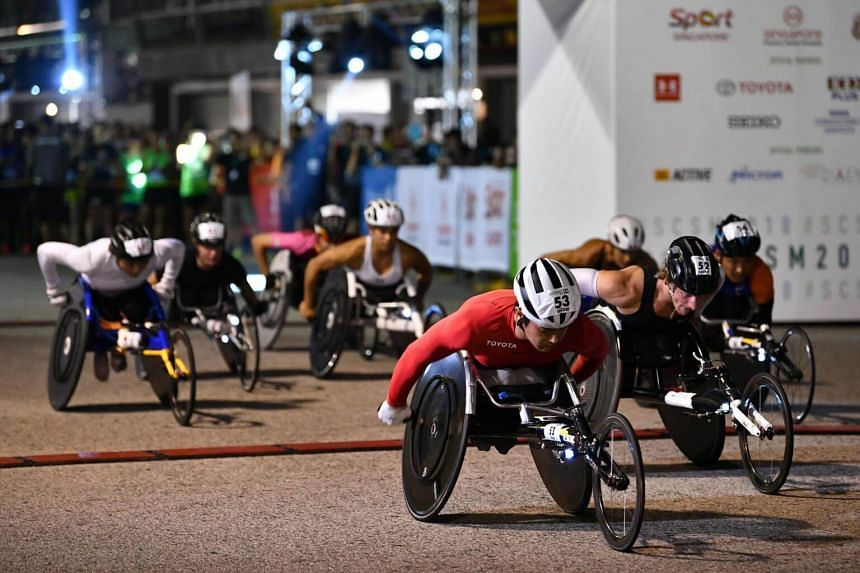 Elite wheelchair racers making a flying start after being flagged off - well before sunrise, at 4.30am - during the Standard Chartered Singapore Marathon at the F1 Pit Building yesterday.