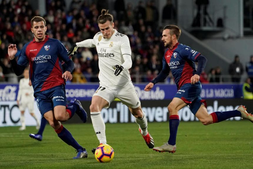 Real Madrid's Gareth Bale in action with Huesca's Christian Rivera and Jorge Miramon in Estadio El Alcoraz, Huesca, Spain, on Dec 9, 2018.