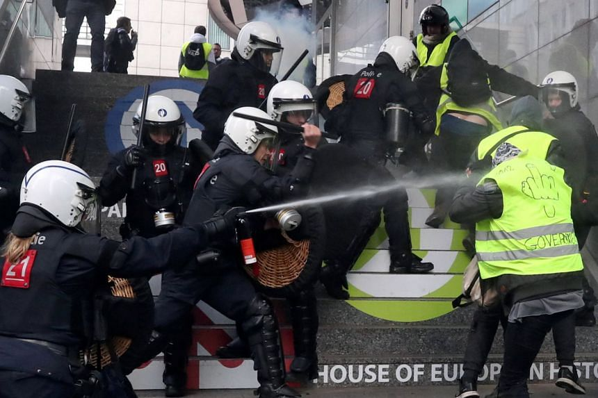 "Demonstrators clashing with the police during the ""yellow vest"" protest over the cost of living and demanding the removal of Belgium's centre-right coalition government in Brussels last Saturday. Police used water cannon and tear gas to keep pe"