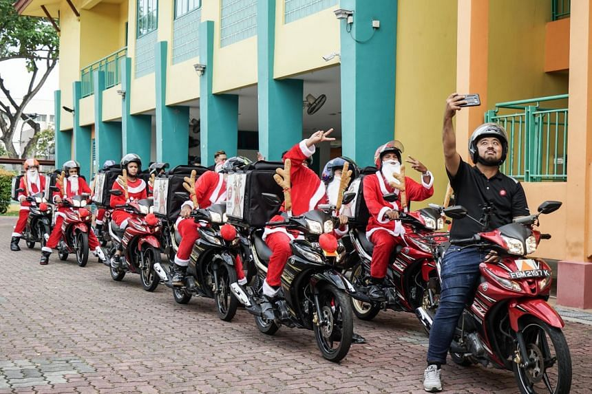 Delivery riders from Pizza Hut Singapore dressed as Santa Claus preparing to take pizzas to the APSN Adult Centre on Dec 7. PHOTO: PIZZA HUT SINGAPORE