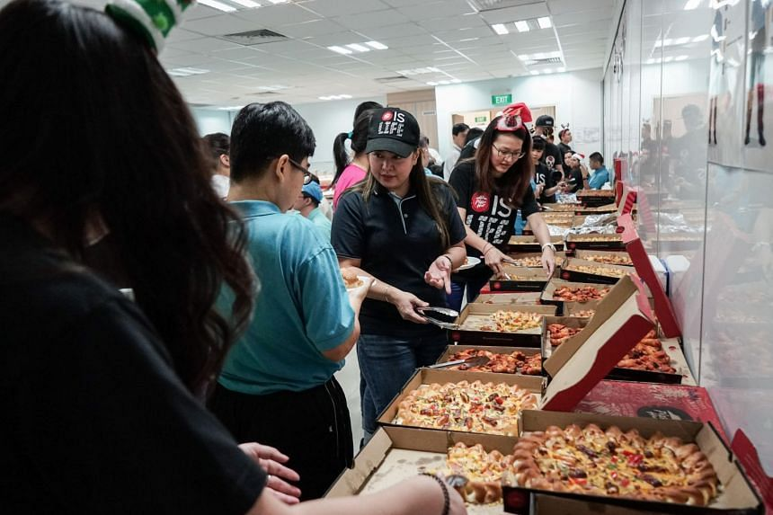 Beneficiaries from APSN Adult Centre enjoying the pizzas together with crew from Pizza Hut Singapore. PHOTO: PIZZA HUT SINGAPORE