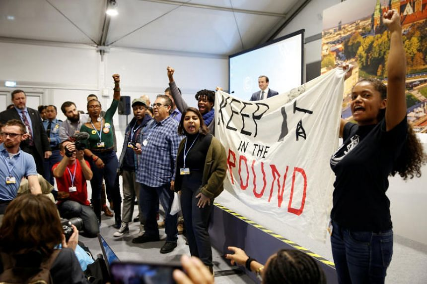 Protesters in the audience seized a microphone and waved banners at the COP24 UN Climate Change Conference 2018 in Katowice, Poland on Dec 10.