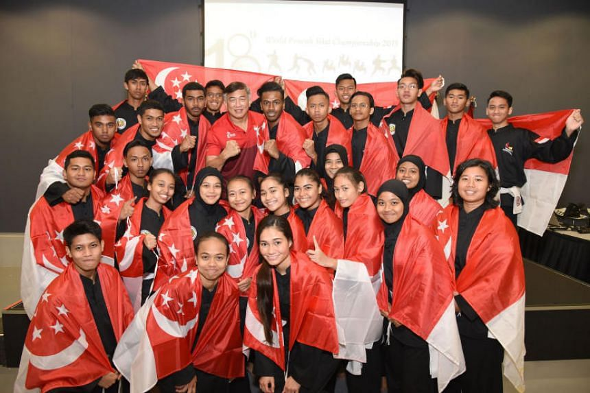 Members of Singapore's silat team poses for a photo with Sport Singapore chief Lim Teck Yin (in red) after the flag raising ceremony held on Dec 10, 2018.