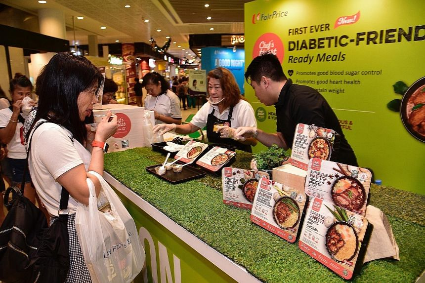 Shoppers tasting the new low-GI ready-to-eat meals at the FairPrice Xtra outlet at AMK Hub yesterday.