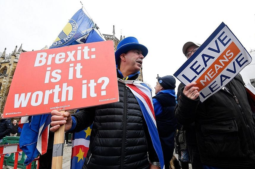Protesters for and against Brexit outside the Houses of Parliament yesterday. Prime Minister Theresa May has postponed a parliamentary vote on Brexit.