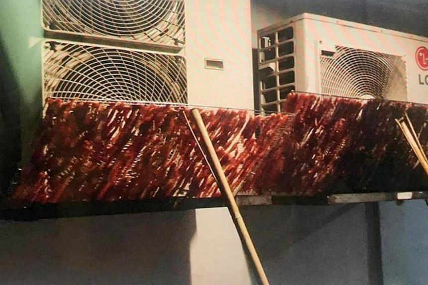 Racks of raw meat being hung to dry outside dusty air-conditioner compressor vents at a HDB block in Beach Road.
