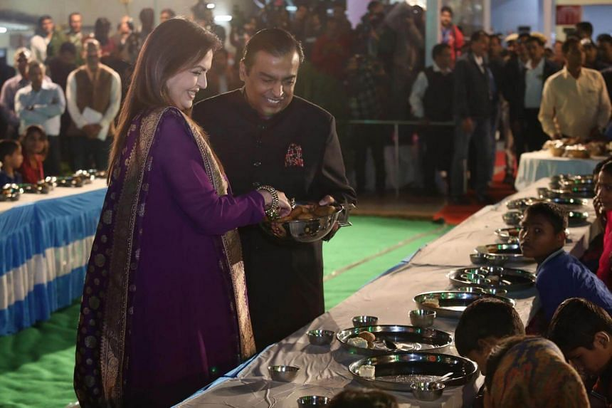 Reliance Industries chairman Mukesh Ambani and his wife Nita serve food to guests during an Anna Seva ritual that coincides with pre-wedding functions ahead of the marriage of their daughter Isha in Udaipur.