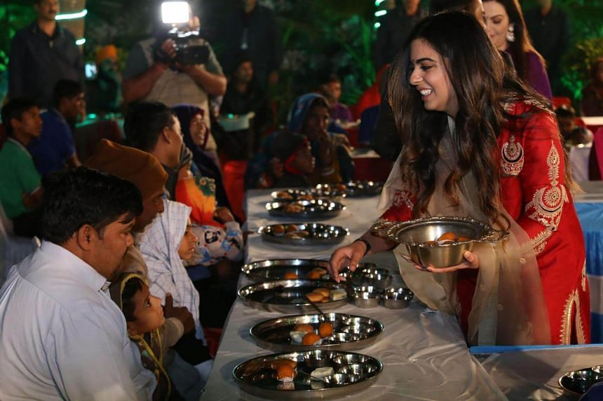 Isha Ambani serves food to guests during an Anna Seva ritual that coincides with pre-wedding functions ahead of her marriage with Anand Piramal, in Udaipur.