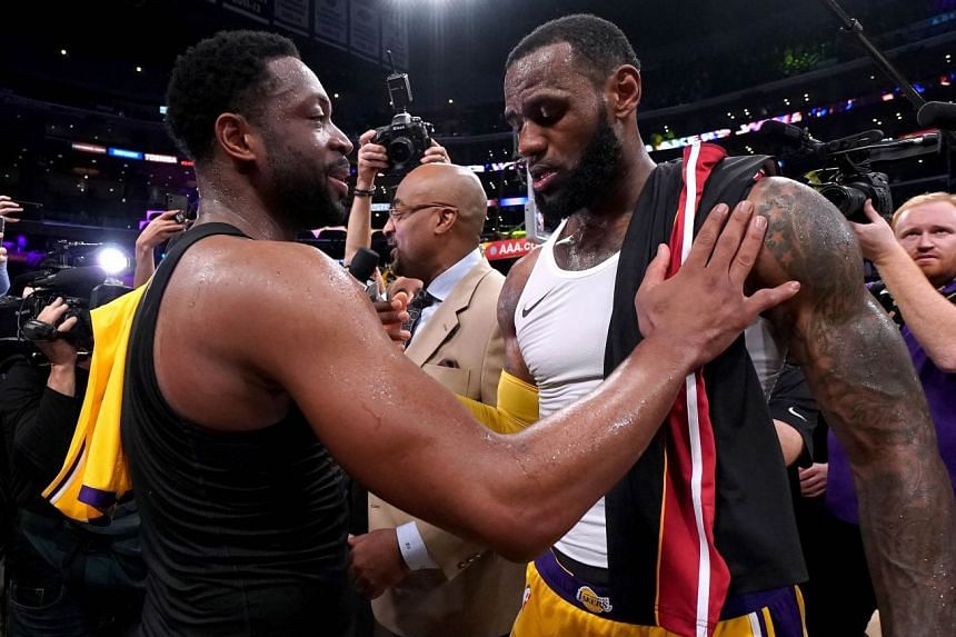 4e38bc978ae6 LeBron James of the Los Angeles Lakers and Dwyane Wade of the Miami Heat  exchange jerseys