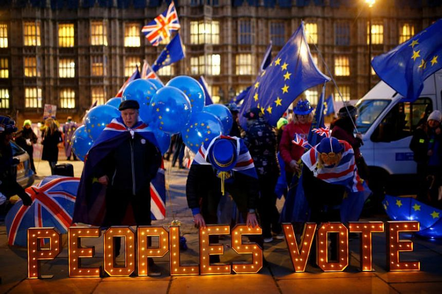 Anti-Brexit protesters stand next to an illuminated sign outside the Houses of Parliament in London, Britain, on Dec 10, 2018.