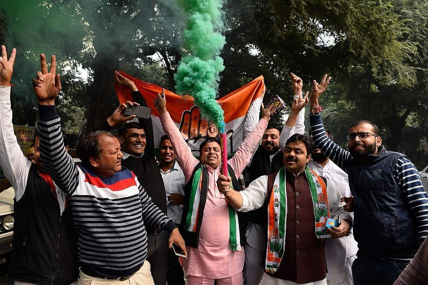 India's Congress party supporters celebrating outside the party headquarters in New Delhi yesterday.