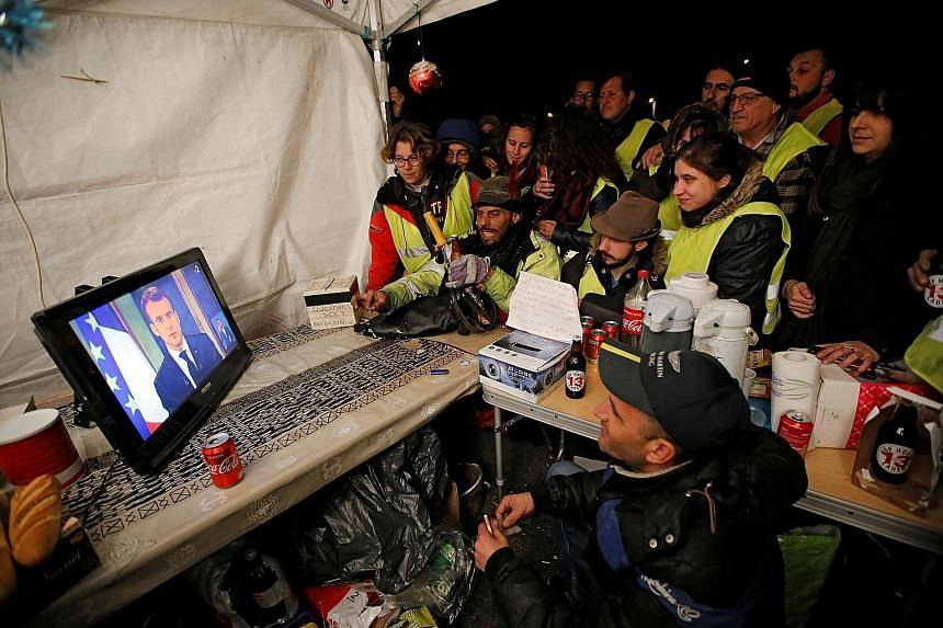 Protesters in yellow vests watching French President Emmanuel Macron on a TV screen at the motorway toll booth in La Ciotat, near Marseille, on Monday. The President's popularity has fallen since he came to power in May last year, with critics saying