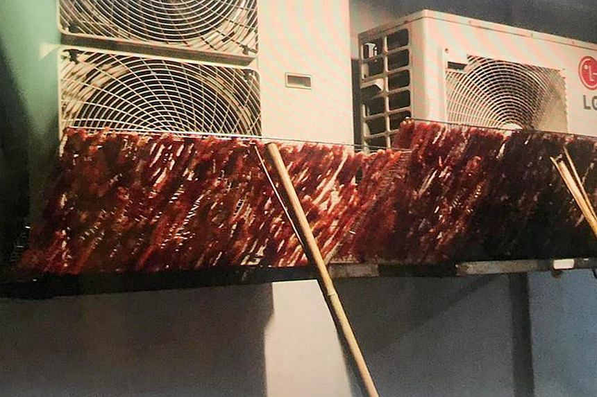 Racks of raw meat drying in front of dusty air-conditioner compressor vents outside an HDB block in Beach Road. The National Environment Agency has advised members of the public not to purchase food prepared in poor-hygiene conditions as the food may