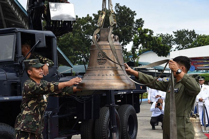 Philippine military personnel unloading one of the three Balangiga church bells after it arrived from the US at a military air base in Manila 	yesterday. The bells were seized 117 years ago as war booty by the US.