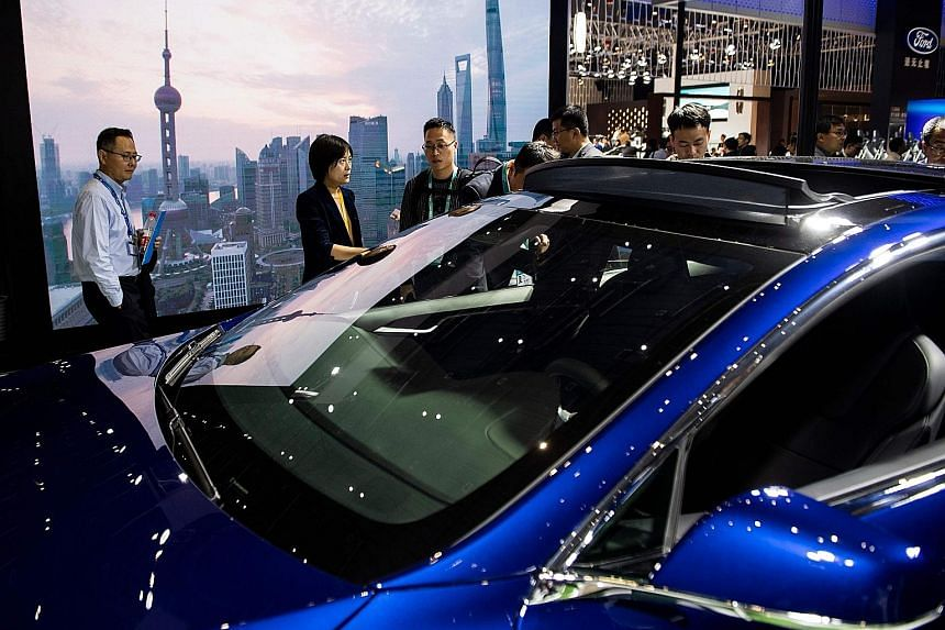 Visitors looking at a Model S car by Tesla Motors during the first China International Import Expo in Shanghai last month. China is reported to be moving towards cutting its trade-war tariffs on US-made cars. Shares of carmakers, including Daimler, F