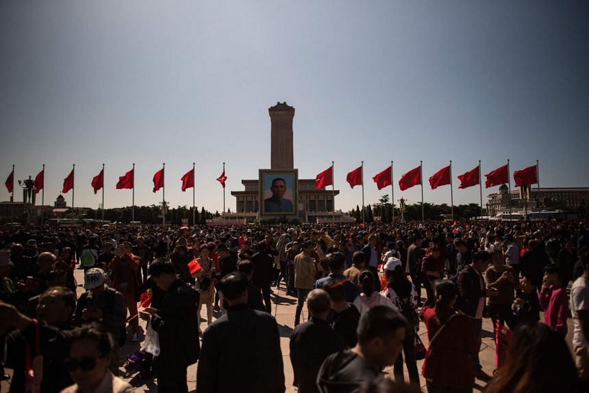 People gather at the Monument to the People's Heroes in Tiananmen Square during National Day in Beijing, on Oct 1, 2018.